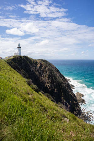 Lighthouse on a cliff by the sea. Vertical picture. Cape Byron. Byron Bay, New South Wales NSW, Australia Stock fotó