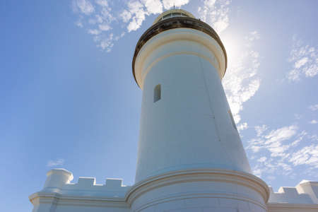 White lighthouse building, pictured from below. Sun behind the lighthouse. Cape Byron, Byron Bay, NSW, Australia