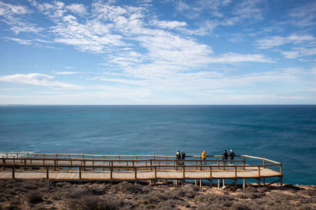 Group of people watching whales migration from an observation platform at the shore. Group of people. Winter time. Nature and ocean observation. Wide angle. Head of Bight, Nullarbor, South Australia