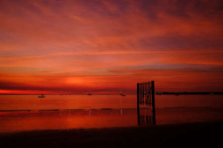 Very intense impressive sunset with orange and red colors, minutes after the sun hid. Picture taken in front of Darwin sailing club. Vesteys beach, Darwin, Northern Territory NT, Australia, Oceania