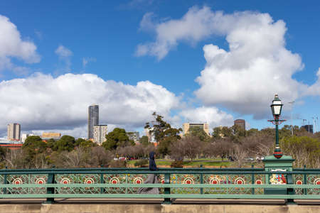 Person walking by the Albert bridge, named after Queen Victoria's husband, Prince Albert. Park and high buildings from the city at the background. Adelaide, Australia