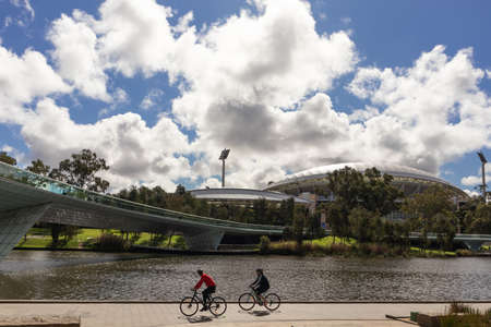 Two people cycling in front of the Adelaide Oval, sports stadium used for cricket, Australian football and rugby. Stadium built next to river Torrens (Karrawirra Parri). Adelaide, South Australia