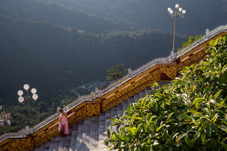 Female buddhist monk walking down the stairs. Nun wears traditional pink and orange clothes, shaved head. Kyaiktiyo Golden rock pagoda, Mon state, Myanmar, Burma, South east Asia Фото со стока