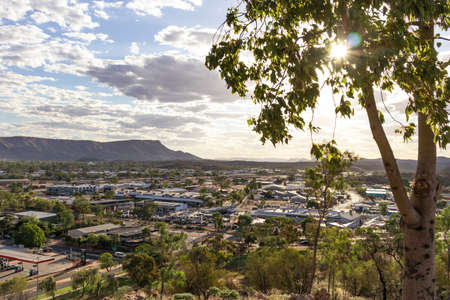 Views of Alice springs township from Anzac hill. Mountains MacDonnell ranges at background. Sun shining among the tree leaves at sunset time. Cloudy sky. Alice Springs, Australia