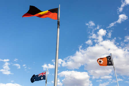 Flags flapping, moved by wind. Three flags from Australia, Northern Territory and Aboriginal flag. Anzac Hill Memorial, Alice Springs, Australia