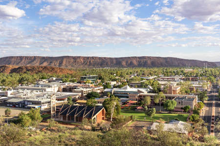 Views of Alice Springs township from Anzac hill. Mountains MacDonnell ranges close to the city. Houses, school and warehouses. Alice Springs, Stuart highway, Red center of Australia