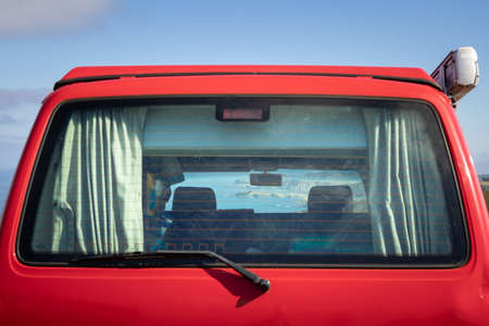Spain; Sep 2020: Views of the ocean and the coastline through the rear window of an old van. Red campervan parked in front of the sea. Low cost touristic route by the Atlantic ocean, Asturias, Spain