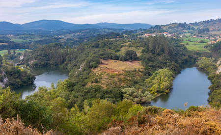 Lookout on the Nora river, surrounded by forests and trees. Mountains and hills at the background. Water meanders near Priañes, Asturias, North of Spain