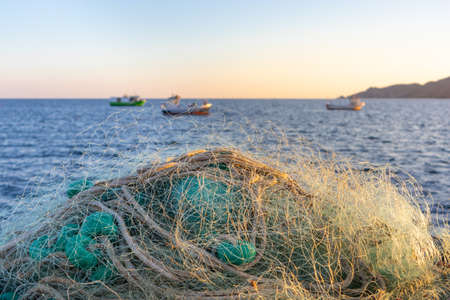 Traditional fishing net and small fishing boats behind. Traditional jobs by the Mediterranean sea. Sunset time, blurry background. Cabo de Gata, Almería, Andalusia, South of Spain