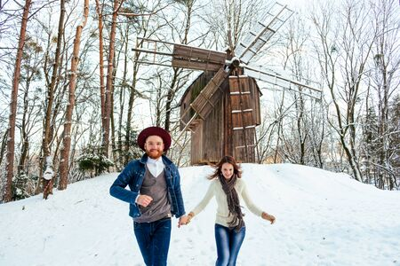 loving happy young couple emotionally runs in the winter woods.