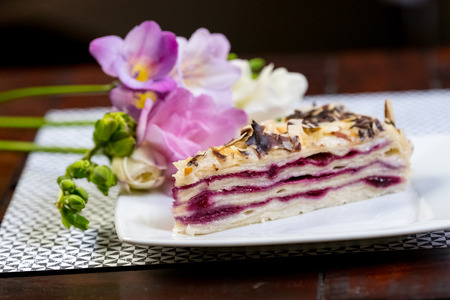 chocolaty: Blueberry Vanilla Cake Piece of cake on a white plate with flowers close-up. Stock Photo