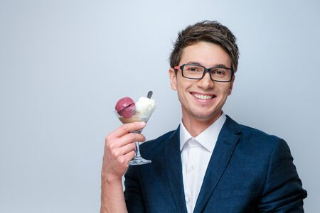 Handsome young man with glasses, a blue jacket and white shirt with ice cream balls in a transparent glass in the studio 免版税图像