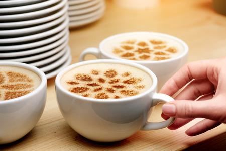 A lot of cups of coffee and a plate with a fire. Cappuccino coffee. A cup of latte, cappuccino or espresso coffee with milk. Drawing the foam milk on top.