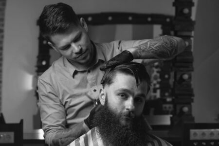comb: Handsome bearded man is looking forward while having his hair cut by hairdresser at the barbershop