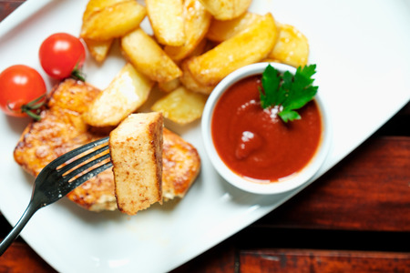 cellulose: Vegetarian dinner. Fried tofu with spices, potatoes with fresh tomatoes. On a white plate, wooden background.