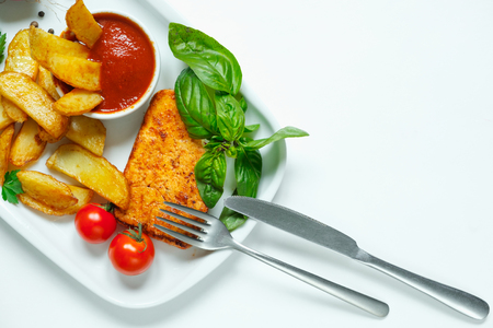 Baked potato wedges with cheese and herbs and tomato sauce on white plate. Close up.