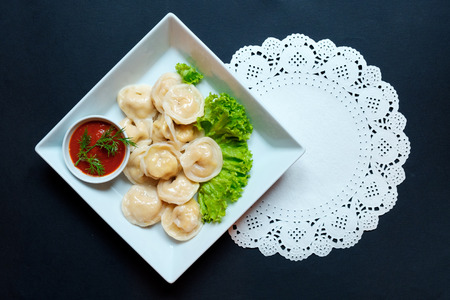 Dumplings raw on a wooden board. Vegeterian food. The process of cooking dumplings.