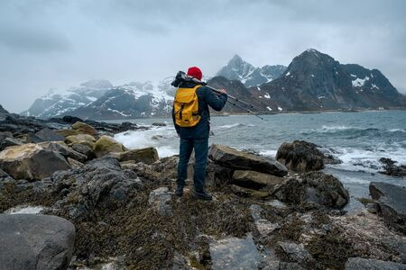 Young man photographer standing at rock in the mountains at Beach photographing the landscapes on Lofoten Islands in Norway.