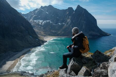 Man sitting on cliff edge alone enjoying aerial view backpacking lifestyle travel adventure outdoor vacations in Norway top of Reinebringen mountain. Stockfoto