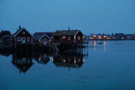 Norway rorbu houses and mountains rocks over fjord landscape scandinavian travel view Lofoten islands. Night landscape.