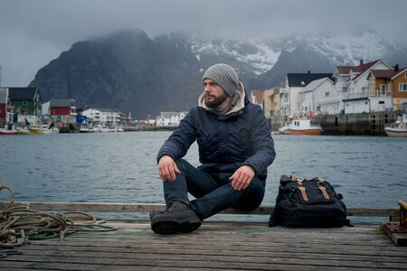 Close up portrait of serious man of Norway pier, background boat