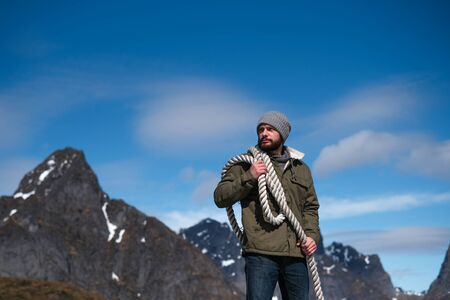 Brutal man with a rope on his shoulder against the background of the mountains and the blue sky. Copy space. Can use as banner