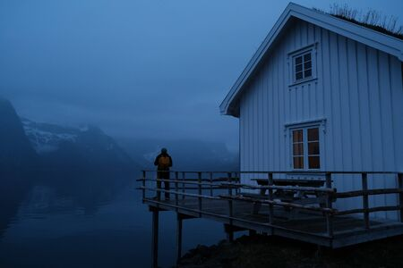 Traveler man with a yellow backpack standing on the background of night Lofoten Reine