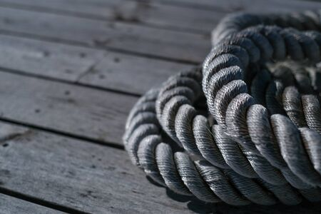 Close up of worn out thick mooring rope on wooden pier. Can use as banner Stockfoto