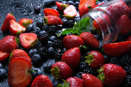 Cooking raspberry and blueberry berry jam. Place in a glass jar.. rotation on a black background