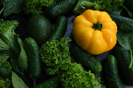 Fresh vegetables, yellow bell peppers, cucumber and salad on a black background.