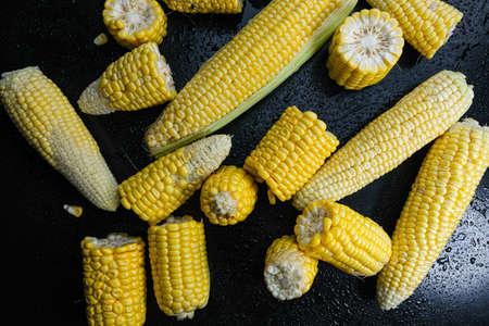 Fresh raw sweet corn cobs on black background Stok Fotoğraf