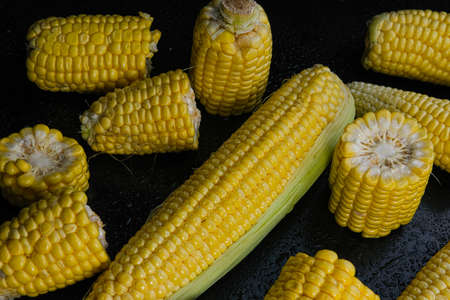Fresh raw sweet corn cobs on black background Stock fotó