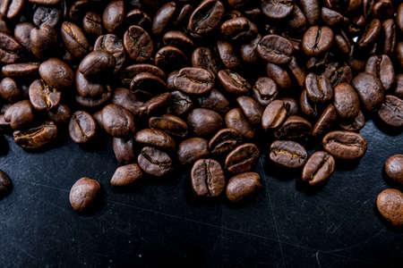 Brown roasted coffee beans, seed on dark background. Espresso dark, aroma, black caffeine drink. Closeup energy mocha, cappuccino ingredient. Stok Fotoğraf