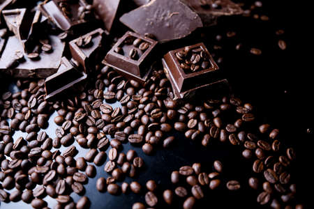 dark organic chocolate and coffee beans on concrete background