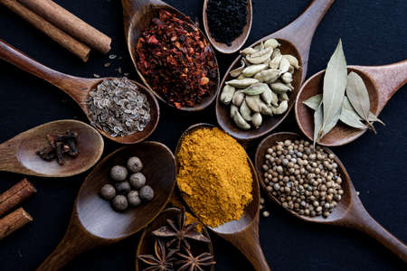 Colourful various herbs and spices for cooking on dark background. Stock fotó