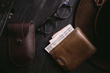 Old money bills in a vintage wallet. Flat lay of travel wooden desk