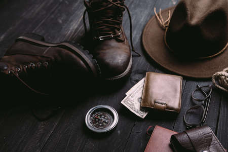 Flat lay of travel things on vintage wooden desk