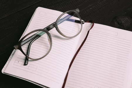 Flat lay of travel things on notepad with glasses on wooden board
