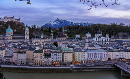 Salzburg / Austria - May 11, 2018: There were a few tourists walking along Salzach River nearby the old town during in the evening in Slazburg.