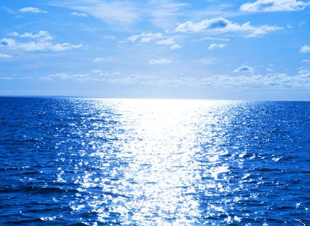 Bright sun path under blue sky with clouds in Atlantic Ocean
