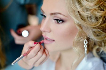 Wedding makeup artist making a make up for bride.