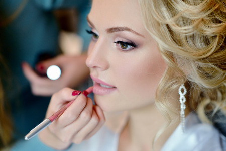 Wedding makeup artist making a make up for bride. Reklamní fotografie - 63512982