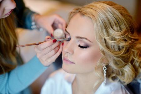 Bruiloft make-up artist het maken van een make-up voor de bruid. Stockfoto