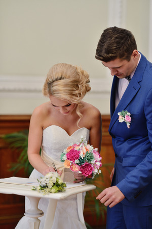 Beauty bride and handsome groom are registering the marriage.