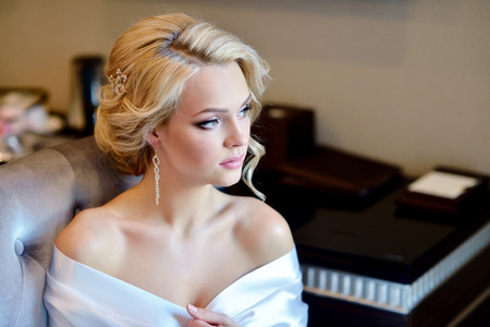 Beauty bride in dressing gown with bridal makeup indoors.