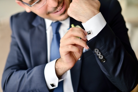 cuff link: Groom is wearing cuff-links indoors. Stock Photo