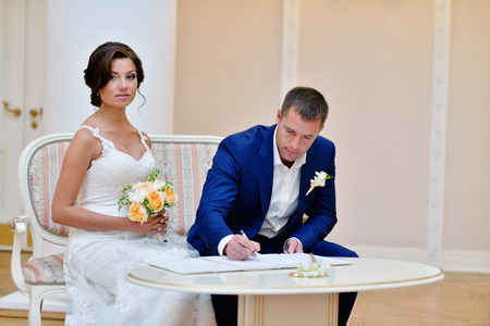 registering: Beauty bride and handsome groom are registering the marriage.