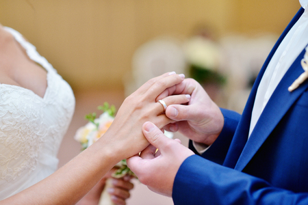 bride and groom are wearing rings each other.