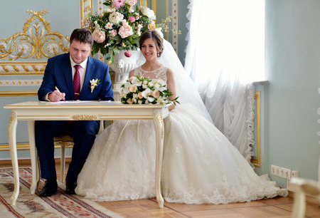 registering: Beauty bride and handsome groom are registering the marriage. Wedding couple is marrying. Beautiful model girl in white dress and in lace veil. Man in suit. Female and male portrait. Cute lady and guy