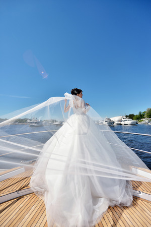 seduce: Beauty bride in bridal gown with lace veil on a yacht. Beautiful model girl in a white wedding dress. Female portrait on the nature. Woman with hairstyle. Cute lady outdoors